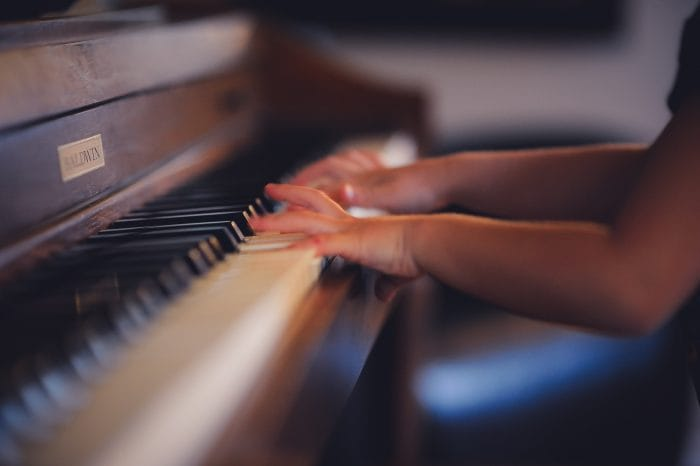 A child's hands playing a children's piano