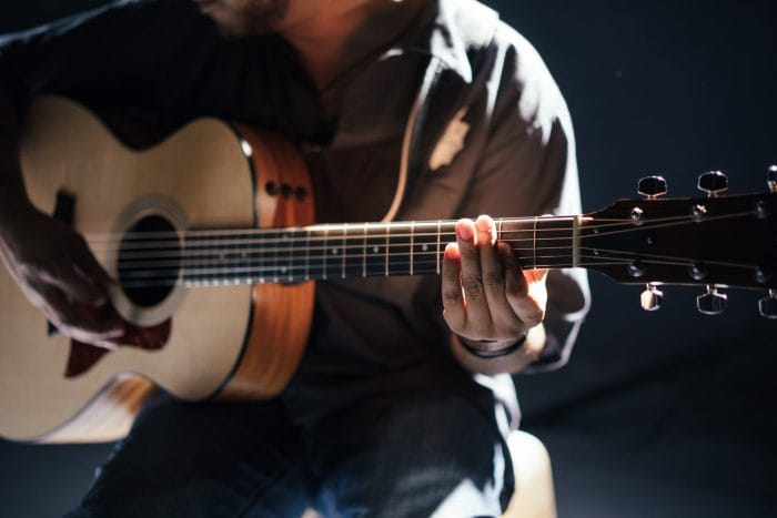 A man sat down playing an acoustic guitar.